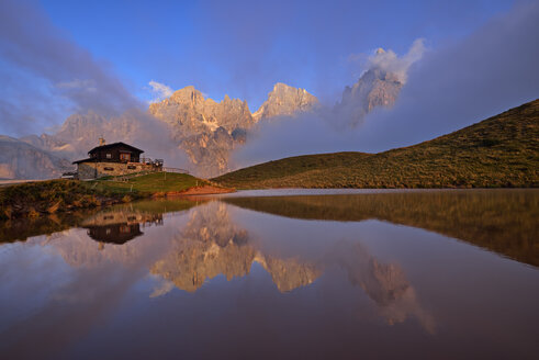 Italy, the mountain group with the mountain Pale di San Martino with Cimon della Pala reflecting in small lake at sunset, Rifugio Baita Giovanni Segantini - RUEF02158