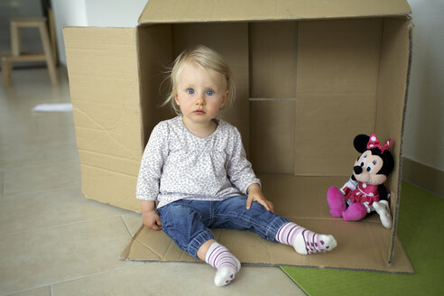Portrait of little girl sitting on the floor of children's room in front of cardboard box - GA00135