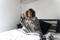 Woman sitting on bed, drinking coffee, using smartphone and earphones - FMOF00539