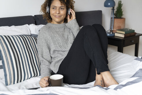 Woman sitting on bed, drinking coffee, listening music with headphones and smartphone - FMOF00545