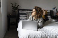 Woman lying on bed, using laptop, surfing the net - FMOF00551