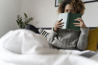 Woman sitting on bed, reading book - FMOF00554