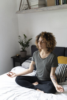 Woman practicing yoga, sitting on bed, meditating - FMOF00563