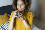 Woman sitting on bed, taking a break, drinking coffee - FMOF00566