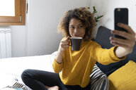 Woman sitting on bed, taking selfies, drinking coffee - FMOF00572