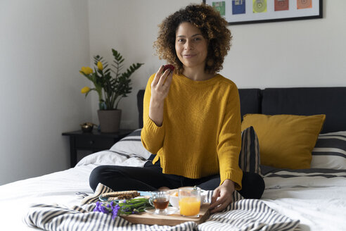 Woman sitting on bed, having a healthy breakfast - FMOF00575