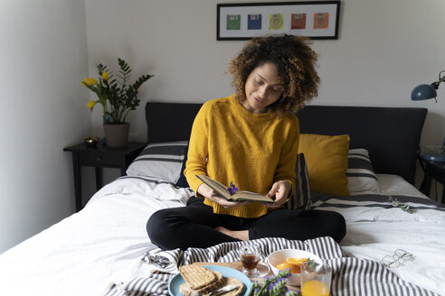 Woman sitting on bed, having a healthy breakfast, reading book - FMOF00578