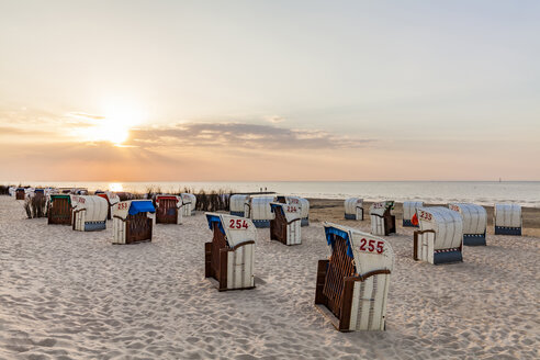 Germany, Lower Saxony, Cuxhaven, Duhnen, beach with hooded beach chairs at sunrise - WDF05243