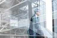 Digital composite businessman looking through modern window - HEROF35808