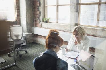 Businesswomen reviewing paperwork in meeting - HEROF35856