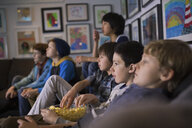 Boys eating popcorn watching TV living room sofa - HEROF35940