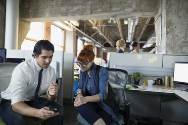 Businessman showing businesswoman cell phone in office - HEROF35955