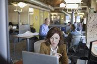 Businesswoman using laptop in office - HEROF35958