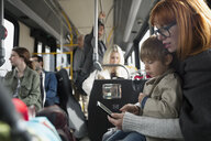 Mother and son using cell phone riding bus - HEROF35982