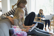 Mother and daughter using digital tablet on sofa - HEROF36009