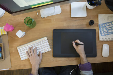 Overhead view of designer using graphics tablet at computer - HEROF36027