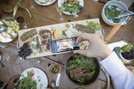Man photographing cheese board with camera phone - HEROF36051