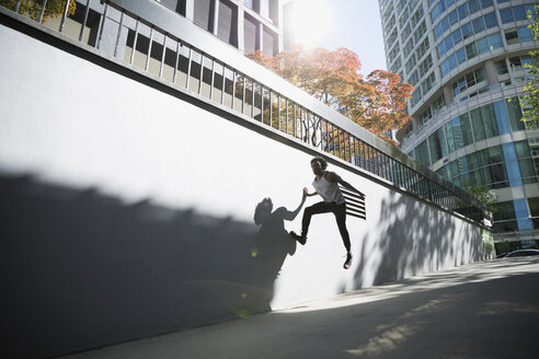 Man jumping against wall in city - HEROF36054