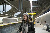 Portrait smiling woman waiting on subway station platform - HEROF36060