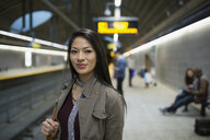 Portrait smiling young woman on subway station platform - HEROF36069