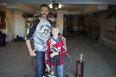 Portrait smiling father and son with trophies in garage - HEROF36099