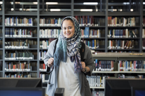 Portrait smiling college student wearing hijab in library - HEROF36135
