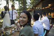 Portrait smiling woman drinking white wine at wedding reception - HEROF36165
