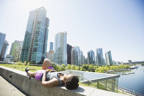 Runner resting laying on ledge at city waterfront - HEROF36183
