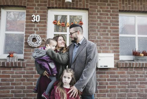 Krefeld, NRW, Deutschland. Eine glückliche Familie mit zwei Kinder stehen draussen vor dem Haus - KMKF00834