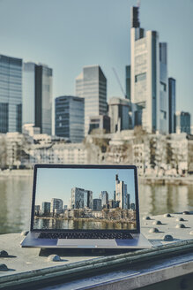 Germany, Frankfurt, laptop with photo of financial district on screen - FMKF05540