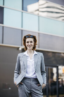 Portrait of a successful young businesswoman in the city, with hands in pockets - JRFF03046