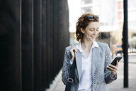 Businesswoman with smartphone, commuting in the city - JRFF03058