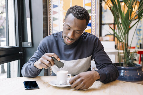 Young man with wireless earphones and cell phone drinking coffee in a coffee shop - OCMF00400