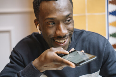 Close-up african man with mobile phone sending an audio message. - OCMF00406