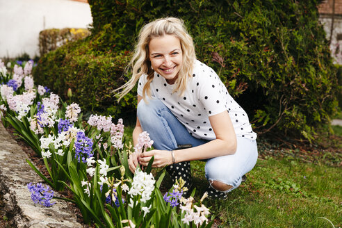 Young blonde woman controls hyacinths in her garden - HMEF00294