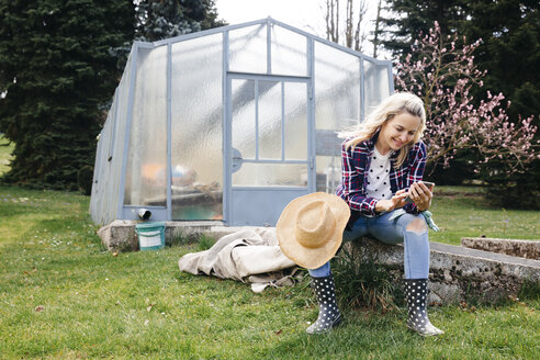 Young woman with a straw hat sitting in front of a greenhouse and looking on her mobile phone - HMEF00306