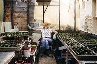 Young woman gardening in a greenhouse - HMEF00321