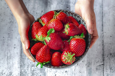 Bowl with fresh strawberries, hands of a girl - SARF04231