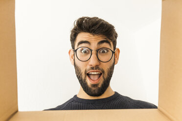 Portrait of surprised young man with beard and glasses looking into cardboard box - TCF06077