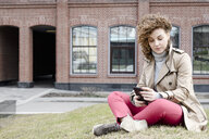Portrait of woman with curly hair sitting on a meadow looking at cell phone - EYAF00155