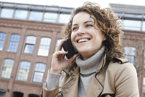 Portrait of young and happy curly woman in trench coat with smartphone - EYAF00158