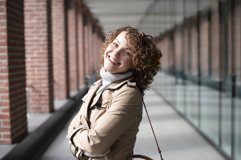 Portrait of happy woman with curly hair wearing beige trenchcoat and turtleneck pullover - EYAF00161