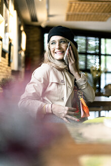 Smiling woman on cell phone in a cafe - ERRF01065