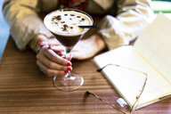 Close-up of woman with a coffee cocktail in a cafe - ERRF01071