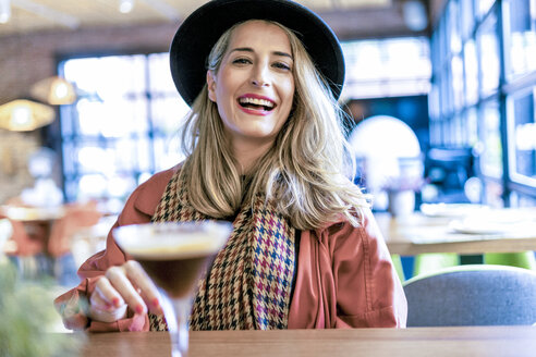 Portrait of happy woman with a coffee cocktail in a cafe - ERRF01074