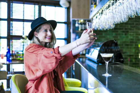 Smiling woman sitting at the counter of a bar taking a selfie - ERRF01083