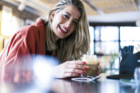 Portrait of happy woman having a drink at the counter of a bar - ERRF01092