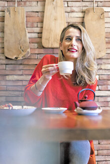 Smiling woman drinking tea in a cafe - ERRF01113