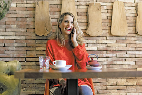 Laughing woman on cell phone in a cafe - ERRF01116