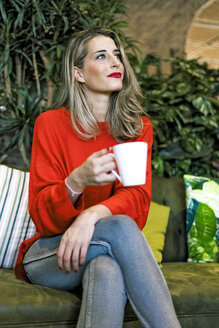 Woman sitting in a cafe holding mug - ERRF01119